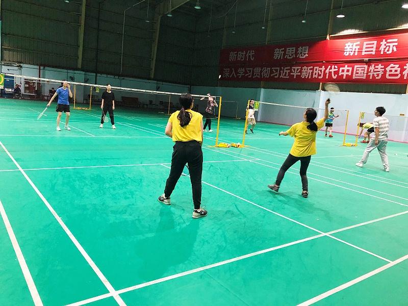图为参加羽毛球活动的现场图